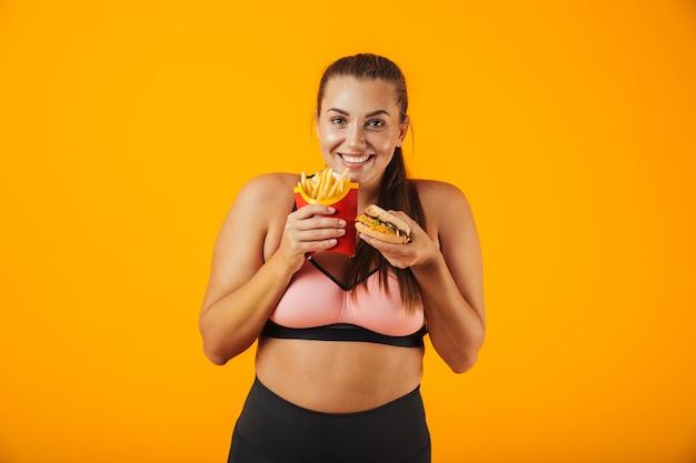 Portret kobiety fitness wesoły nadwaga na sobie odzież sportową stojących na białym tle nad żółtą ścianą