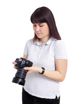 Portret kobiety fotograf lub kamerzysta oglądający wideo lub zdjęcia w swoim aparacie na białym tle