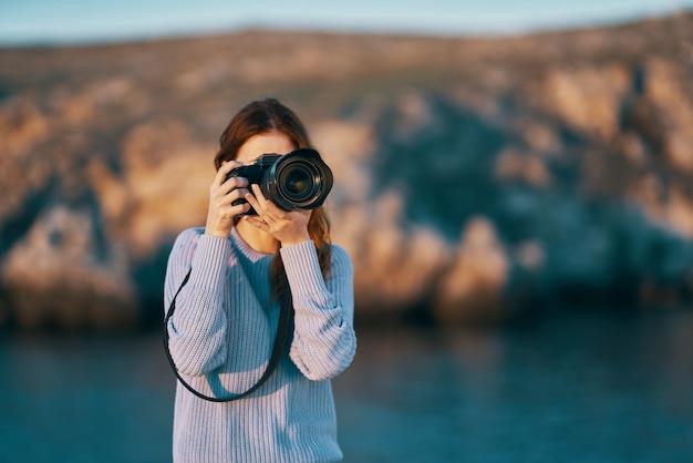 Portret kobiety fotografa z profesjonalnym aparatem w plenerze