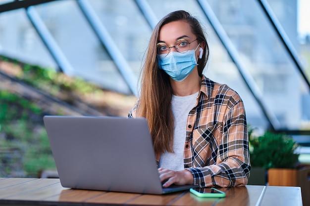 Portret kobiety freelancer w masce ochronnej, bezprzewodowych słuchawkach i okrągłych okularach, zdalnie pracujący online przy komputerze w kawiarni. ochrona zdrowia w miejscach publicznych
