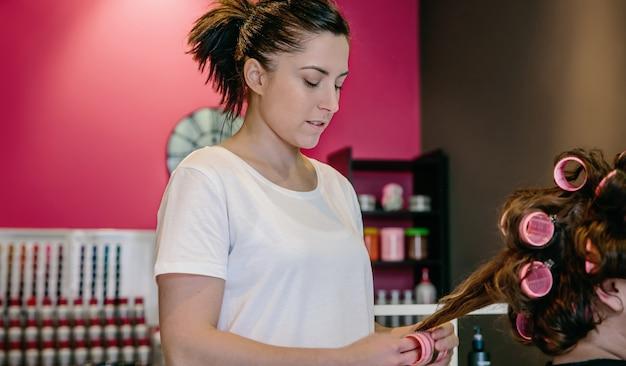 Portret kobiety fryzjer zwijania włosów do klienta za pomocą lokówek w salonie fryzjerskim i kosmetycznym