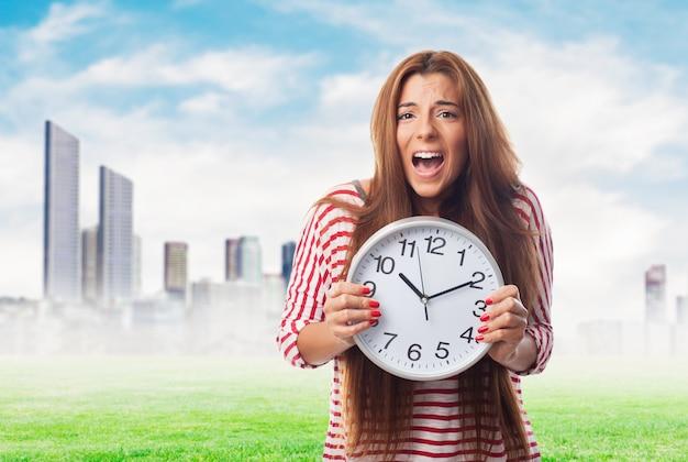 Portret kobiety gospodarstwa zegara i krzyczy