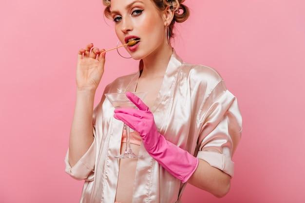 Portret kobiety gryzie oliwkę i trzyma kieliszek martini na różowej ścianie