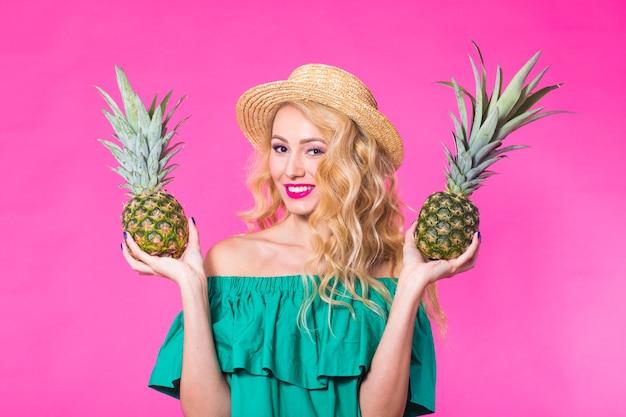 Portret kobiety i ananasa na różowym tle. lato, dieta i zdrowy tryb życia