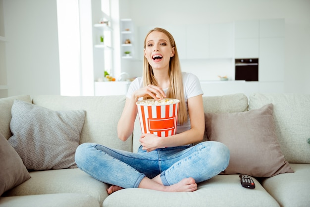 Portret kobiety jedzenie popcornu w domu