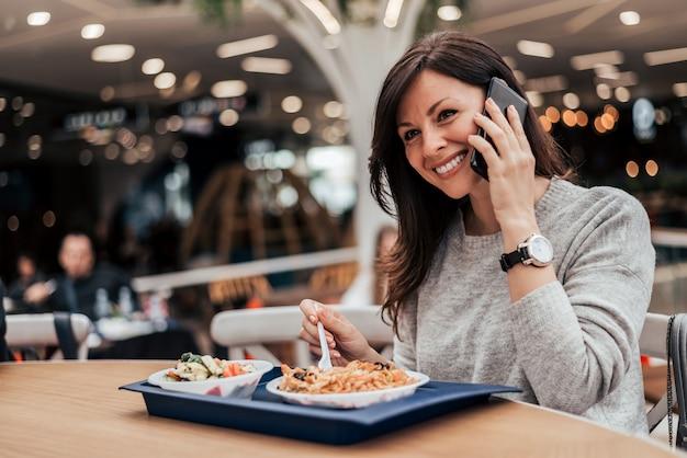 Portret kobiety jedzenie w restauracji fast food i rozmowy na telefon komórkowy.