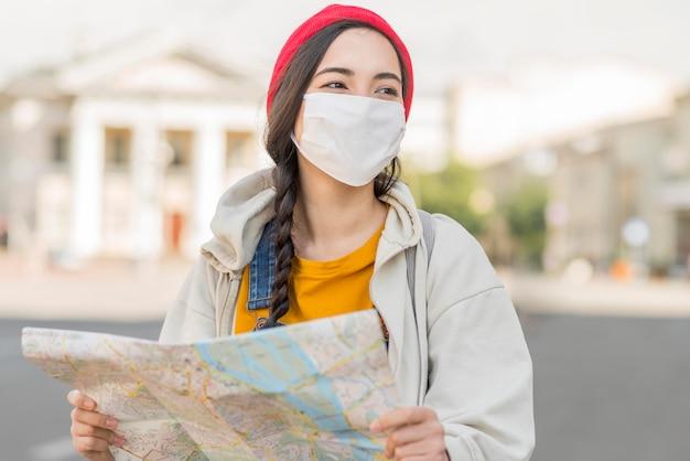 Portret kobiety jest ubranym maskę z mapą