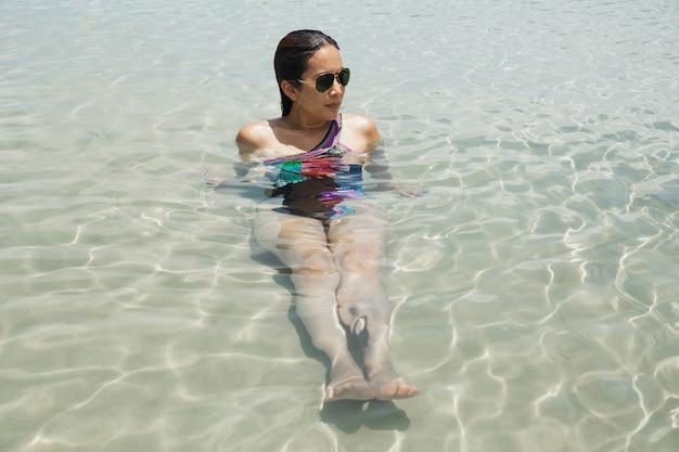 Portret kobiety kąpieli w morzu na wakacje na tropikalnej wyspie.