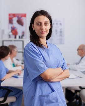 Portret kobiety kardiolog ze stetoskopem, patrzącej z przodu w mundurze medycznym, pracującej w sali konferencyjnej