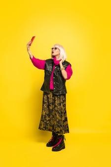 Portret kobiety kaukaski na białym tle na żółtej ścianie, influencer