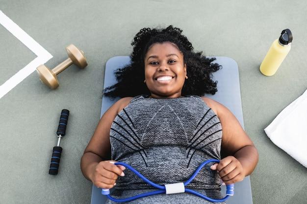 Portret kobiety krzywego robi rutynowego treningu na świeżym powietrzu w parku miejskim