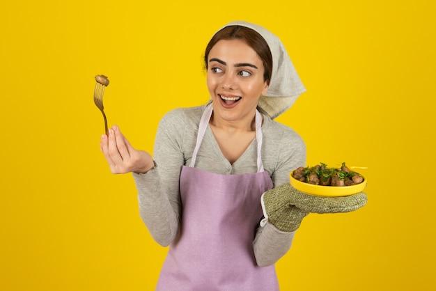 Portret kobiety kucharz w fioletowy fartuch jedzenie smażonych grzybów.