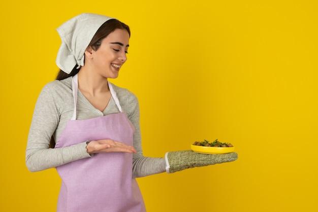 Portret kobiety kucharz w fioletowy fartuch oferujący talerz smażonych grzybów.