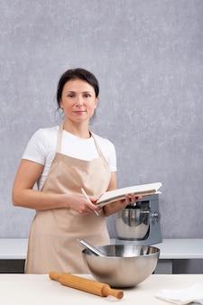 Portret kobiety kucharz w kuchni z książką kucharską w dłoniach. miska i wałek do ciasta na stole. rama pionowa.