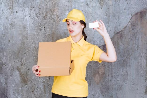Portret kobiety kurierki trzymającej kartę z kartonowym pudełkiem