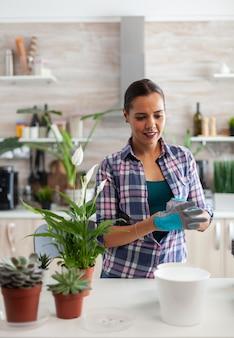 Portret kobiety kwiaciarki pracującej w domu przy użyciu rękawic ogrodniczych