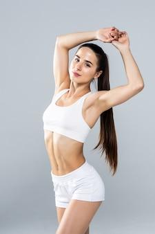 Portret kobiety ładny fitness rozciąganie rąk na białym tle na białym tle