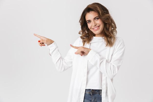 Portret kobiety ładny w ubranie, wskazując palcami na bok, na białym tle