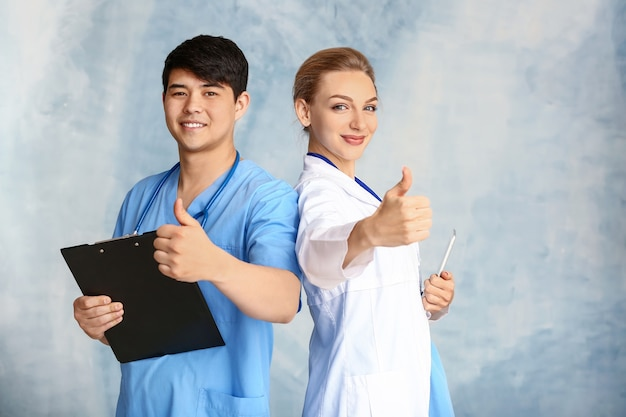 Portret kobiety lekarz i męski asystent medyczny pokazujący kciuk w górę na kolorowym tle