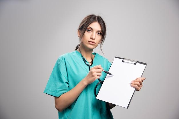 Portret kobiety lekarz pozowanie ze schowka na szaro