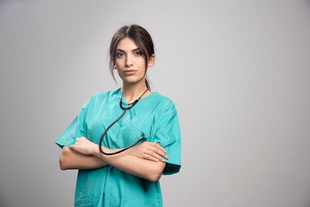 Portret kobiety lekarz pozowanie ze stetoskopem na szaro