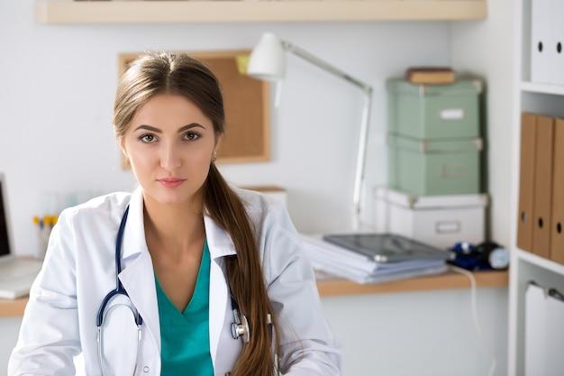 Portret kobiety lekarz terapeuta medycyny siedzi w swoim biurze