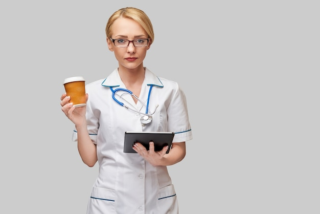 Portret kobiety lekarza trzymając papierowy kubek kawy i trzymając tablet pc pad