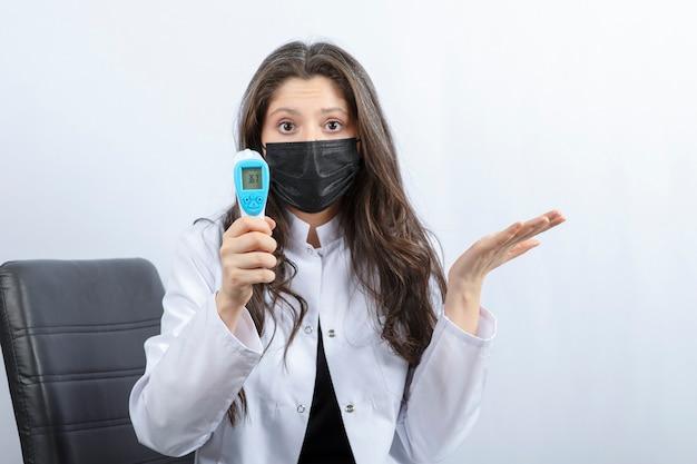 Portret kobiety lekarza w masce medycznej i białym fartuchu, trzymając termometr.