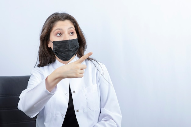 Portret kobiety lekarza w masce medycznej i wskazując biały fartuch.