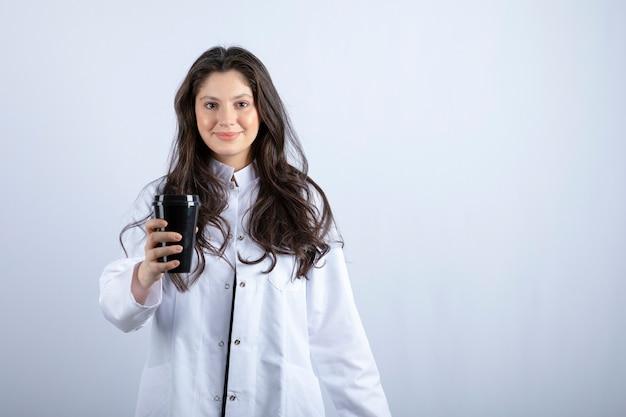 Portret kobiety lekarza z filiżanką kawy na szaro.