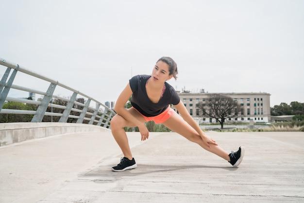 Portret kobiety lekkoatletycznego rozciągania nóg przed ćwiczeniami na świeżym powietrzu. sport i zdrowy tryb życia.