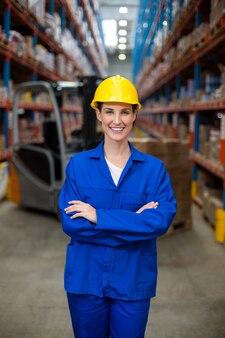 Portret kobiety magazynu pracownika pozycja z rękami krzyżować
