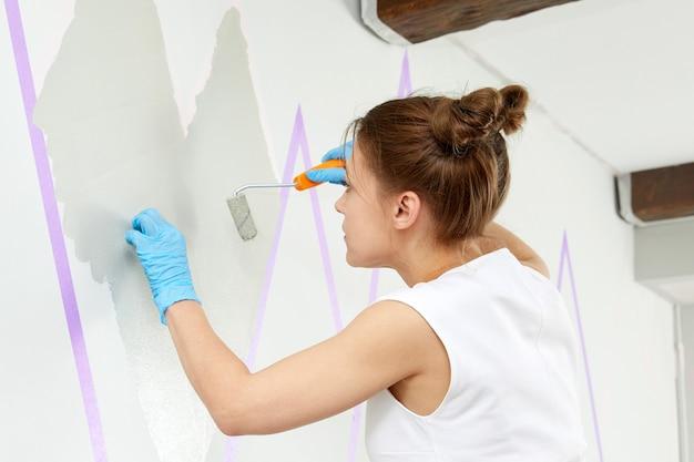 Portret kobiety malującej ornament ścienny za pomocą wałka do malowania i używania taśmy maskującej podczas stania