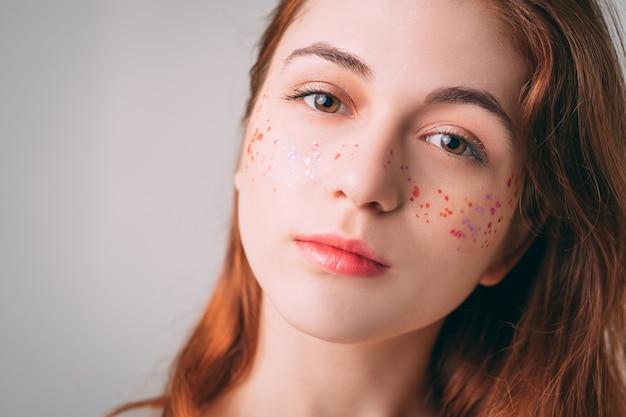 Portret kobiety młode rude. piękno kobiety. naturalny makijaż. trend brokatowych piegów.