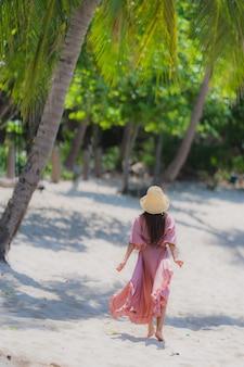 Portret kobiety młody azjatykci uśmiech szczęśliwy wokoło plażowego dennego oceanu z kokosowym drzewkiem palmowym dla wakacje wakacje