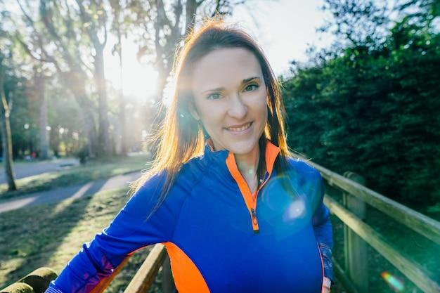 Portret kobiety młody piękny sportowiec podświetlany z flary patrząc na kamery o zachodzie słońca wiosną lub latem w zalesionym parku. koncepcja wizerunku firmy. kobieta i sport