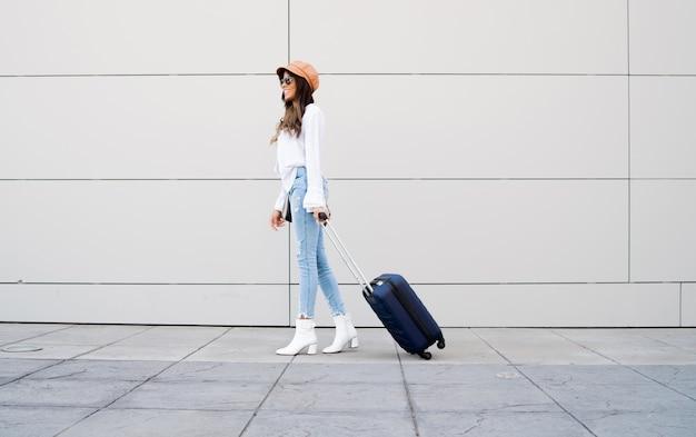 Portret kobiety młody podróżnik niosąc walizkę podczas spaceru na ulicy
