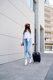 Portret kobiety młody podróżnik ubrany w maskę ochronną i niosący walizkę podczas spaceru na ulicy