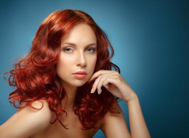 Portret kobiety moda. długie kręcone rude włosy.