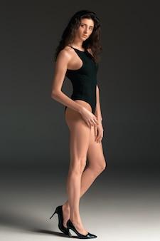 Portret kobiety moda. piękna młoda modelka w czarnym kostiumie kąpielowym. łapka, szare tło.