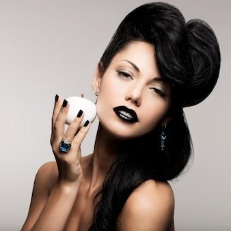 Portret kobiety moda z nowoczesną fryzurę i usta w kolorze czarnym z białym jabłkiem