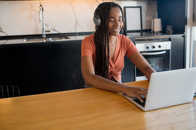 Portret kobiety na rozmowę wideo z laptopem i słuchawkami podczas pracy w domu