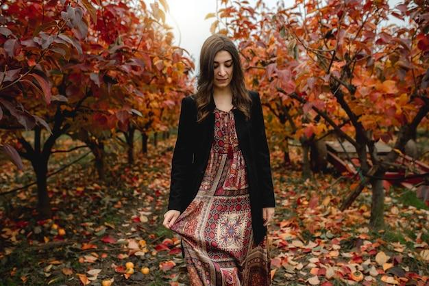 Portret kobiety na sobie sukienkę i koronę kwiatową spacerującą samotnie w polu z czerwonymi drzewami i opadłymi liśćmi w sezonie jesiennym.