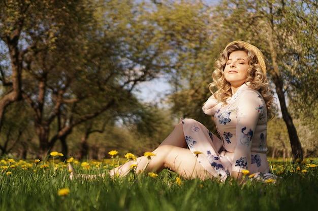 Portret kobiety na zewnątrz. kobieta w słomkowym kapeluszu w kwiatowym polu. lato na wsi