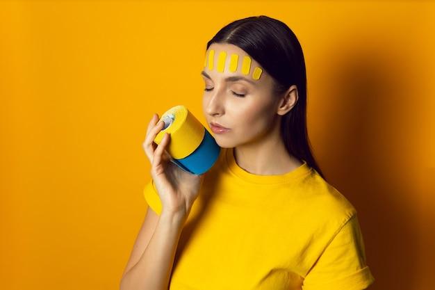 Portret kobiety na żółtej ścianie z kinesiotapą twarzy na czole trzyma rolkę taśm