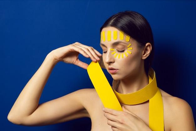 Portret kobiety nago na niebieskiej ścianie z kinesiotapą twarzy na czole trzyma w dłoni rolkę kinesiotapingu