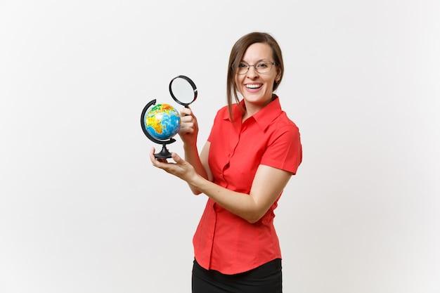 Portret kobiety nauczyciel biznesu w czerwonej koszuli gospodarstwa i patrząc przez szkło powiększające na kuli ziemskiej na białym tle. nauczanie edukacji w koncepcji uniwersytetu liceum. skopiuj miejsce.
