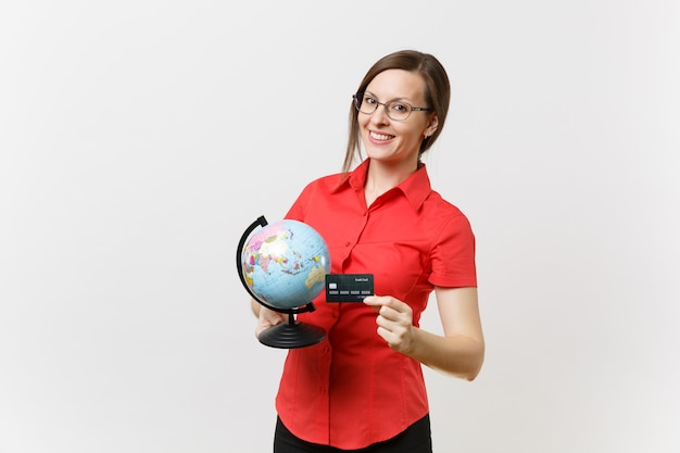 Portret kobiety nauczyciel biznesu w czerwonej koszuli spódnica okulary trzymając kulę ziemską i kartę kredytową na białym tle. nauczanie edukacji na uniwersytecie, turystyka, koncepcja studiów za granicą.