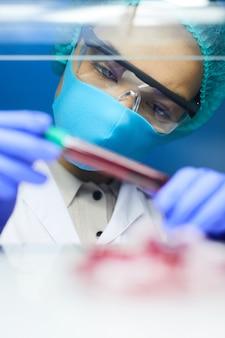 Portret kobiety naukowiec trzymając probówkę z próbką krwi podczas pracy nad badaniami w laboratorium, miejsce