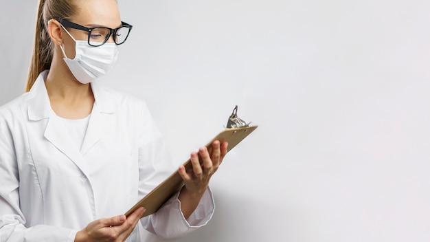 Portret kobiety naukowiec w laboratorium z maską medyczną i schowkiem